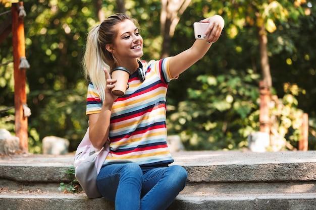 행복 한 귀여운 어린 소녀 커피를 들고 휴대 전화로 selfie를 받아.