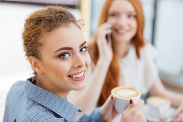 Счастливая милая молодая женщина пьет кофе со своим другом в кафе