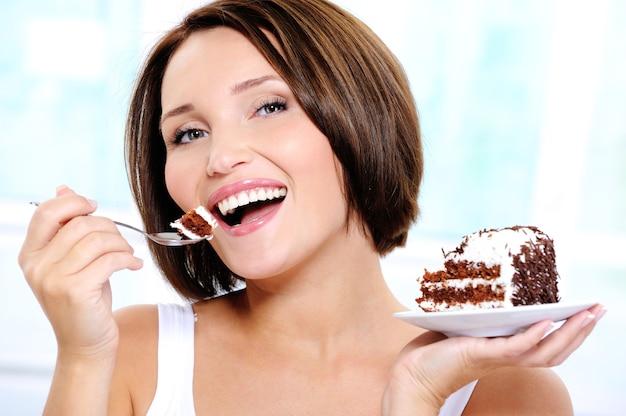 幸せなかわいい若い女性がケーキを食べる