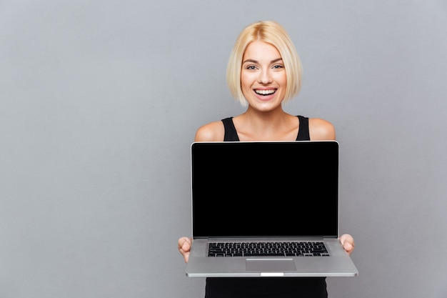 Happy cute young woman holding blank screen laptop over gray wall