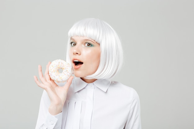 Happy cute young woman holding sweet donut