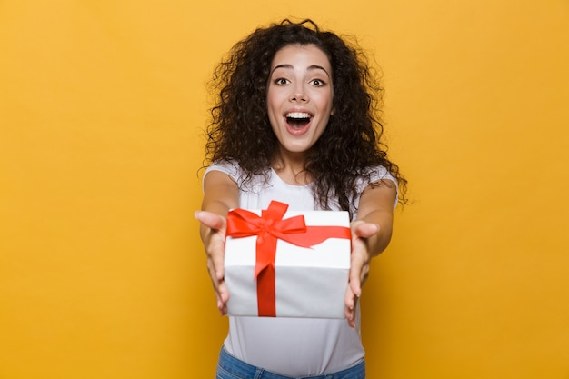 Happy cute young woman posing isolated on yellow holding gift box present.