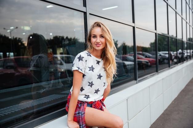 ガラスの建物で屋外に立っているブロンドの髪を持つ幸せなかわいい若い女性