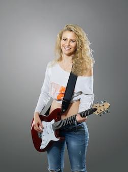 흰색에 스튜디오에서 기타와 함께 행복 한 귀여운 젊은 여자