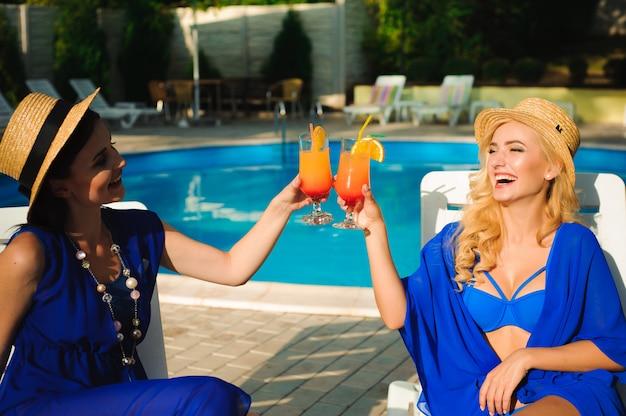 カクテルが笑って、スイミングプールのそばで楽しんで幸せなかわいい若い女性。