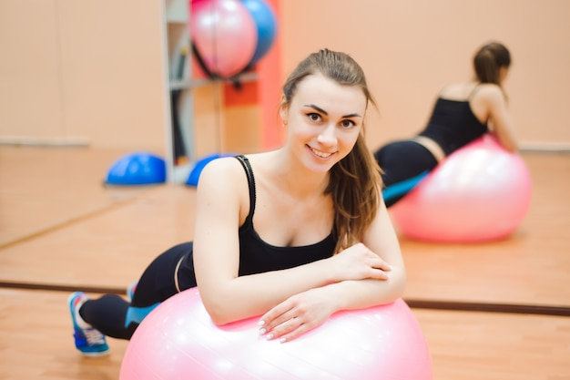 Happy cutie athletic girl , execute exercise and smile, in sport-hall.