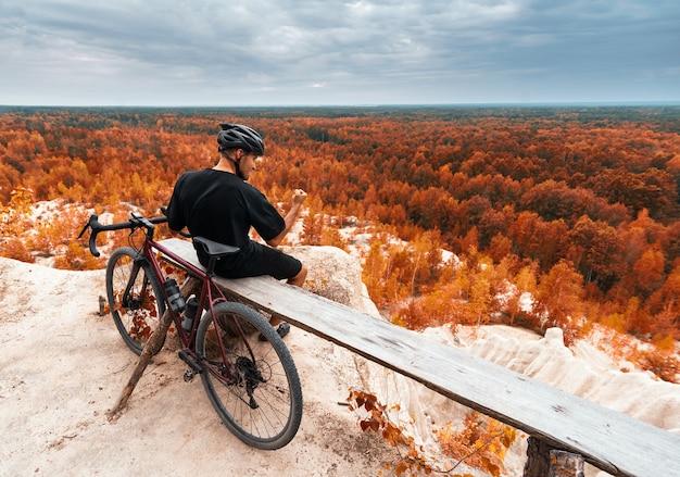 Счастливый велосипедист празднует победу, сжимая кулак в осеннем лесу
