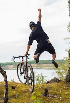 ゴール達成の勝利を祝う幸せなサイクリスト。スポーツトレーニングのコンセプト。アクティブなライフスタイル。