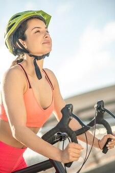 幸せなサイクリスト。幸せで満足しているように見える保護ヘルメットの女性サイクリスト