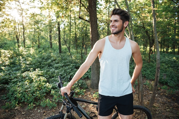 Happy cyclist in forest looking away