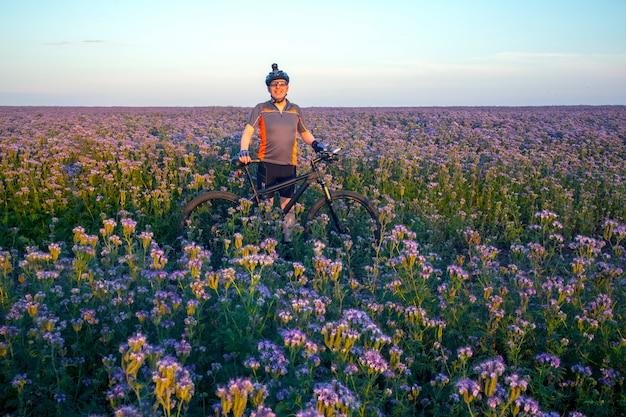 행복한 자전거 타는 사람은 꽃이 만발한 들판에서 자전거와 함께 서 있다