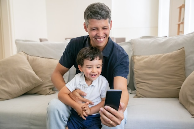 Happy dad and adorable little son having fun together, using phone for video chat while sitting on couch at home