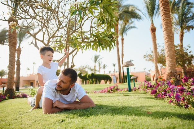 Счастливый папа и ребенок мальчик, наслаждаясь в солнечном парке.