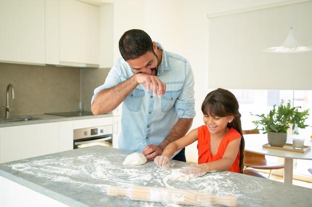 幸せなお父さんと娘が台所のテーブルで生地を練りながら楽しんで。父が少女にパンやパイを焼くように教える。家族の料理のコンセプト