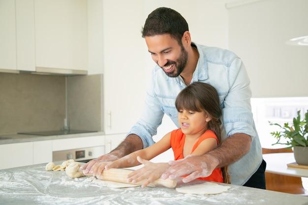 幸せなお父さんと娘が乱雑に小麦粉を台所のテーブルで生地を圧延します。