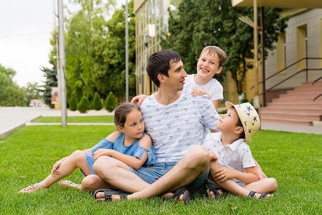 Счастливый папа и его дети на зеленой лужайке. день детей
