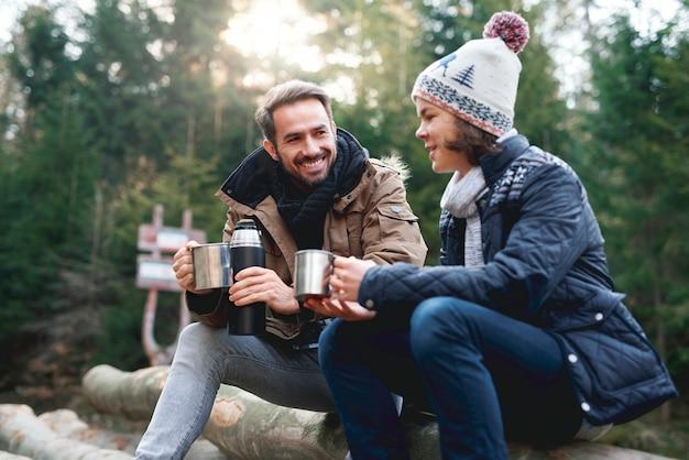 幸せなお父さんと彼の息子が秋の森でお茶を飲む