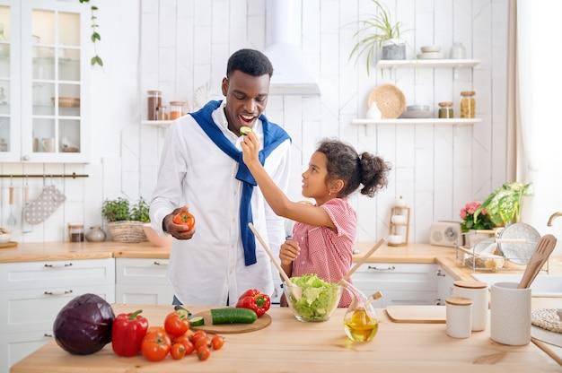 행복한 아빠와 아이가 아침에 야채 샐러드를 요리합니다. 웃는 가족은 아침에 부엌에서 먹습니다. 아버지는 여자 아이를 먹여, 좋은 관계