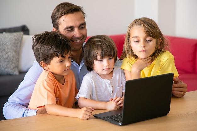 一緒にラップトップを介して映画を見ている幸せなお父さんと子供たち。テーブルに座ってかわいい子供たちを抱きしめる白人の父。画面を見ている男の子と女の子。父権とデジタル技術の概念