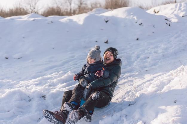 행복 한 아빠와 눈 썰매를 가지고 노는 어린 소년