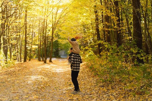 幸せなお父さんと息子が子供連れの家族のために秋の森の秋の野外活動を歩いています