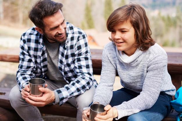 幸せなお父さんと息子が森でお茶を飲む