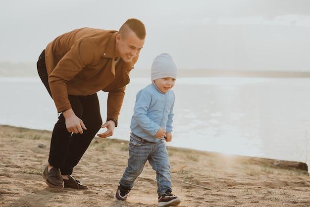 幸せなお父さんと息子は夏に川沿いのビーチの砂で遊ぶ