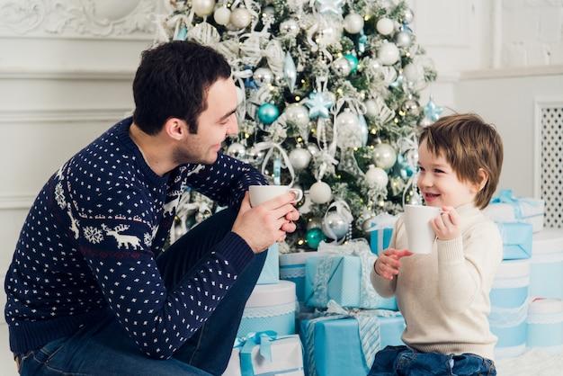 クリスマスにお茶を飲みながら幸せなお父さんと息子