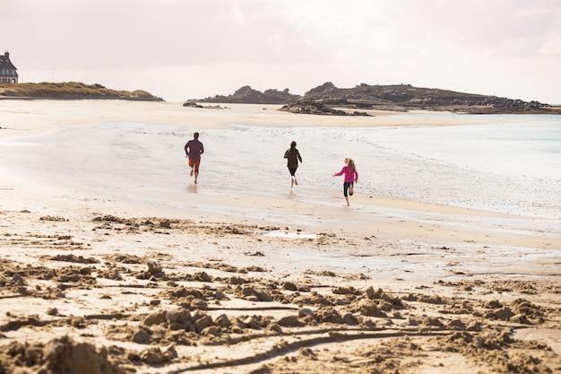 幸せなお父さんと干潮時にビーチに沿って走っている2人の娘。フランス北部のトレガステルにある典型的なブルターニュの海岸