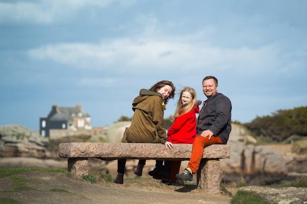 幸せなお父さんと2人の娘が、ブルターニュのトレガステルの海と海岸近くのベンチに座っています。フランス