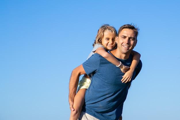 陽気な女の子を背負って幸せなお父さん。屋外で一緒に余暇を楽しんでいる父と娘。家族と屋外ウォーキングのコンセプト