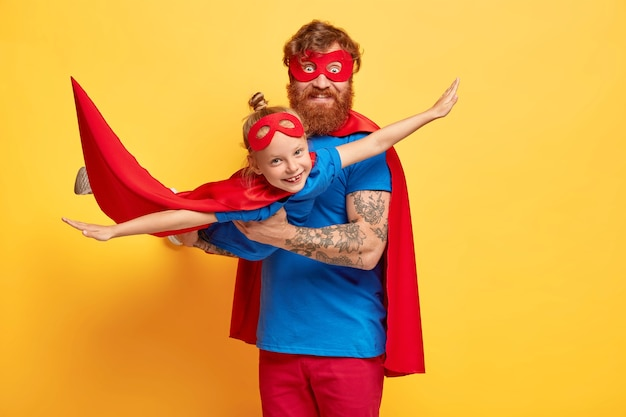 Happy dad and daughter play superhero game