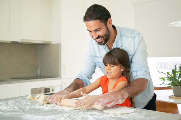 Felice papà e figlia che rotolano la pasta sul tavolo della cucina con farina disordinata.