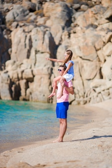 Happy dad and girl having fun on white tropical beach