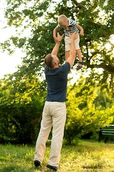 幸せなお父さんは喜んで息子を庭の頭上に投げます。父の日。家族の幸せ、父性、一緒に屋外遊びの概念。