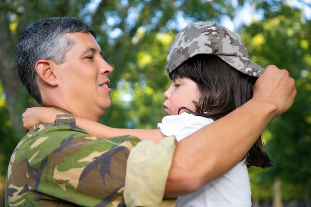 幸せなお父さんは娘を腕に抱き、カモフラージュの帽子をかぶった女の子をドレスアップします。側面図。家族の再会または帰国の概念