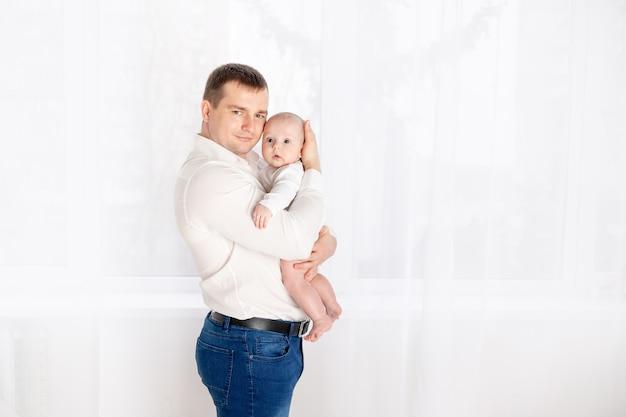 窓際の家で生まれたばかりの赤ちゃんを抱いて幸せなお父さん、幸せな愛情のある家族の概念、父の日