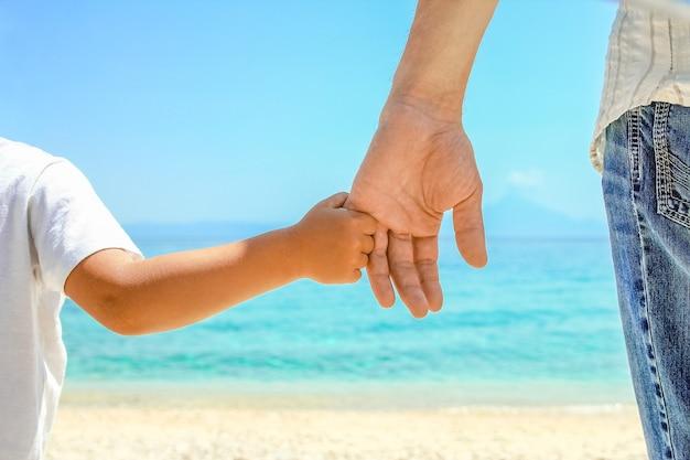 Счастливый папа держит за руку ребенка у греческого моря на природе