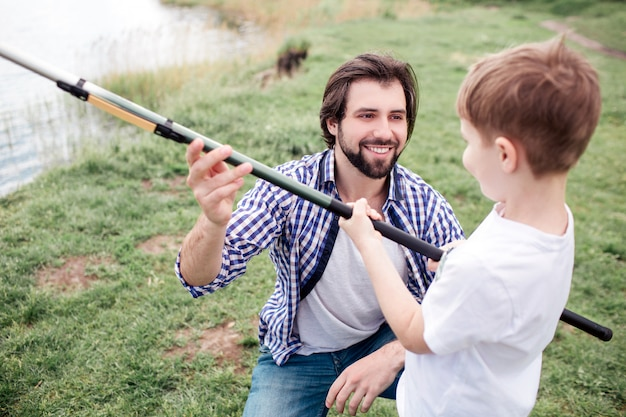 Happy dad is giving fish-rod to his son. he is smiling. boy is holding fish-rod very tight and looking at dad.