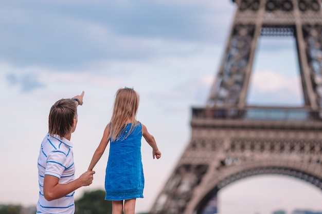 Happy dad and little adorable girl traveling in paris near eiffel tower