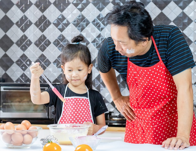 Happy dad and little daughter cooking in kitchen