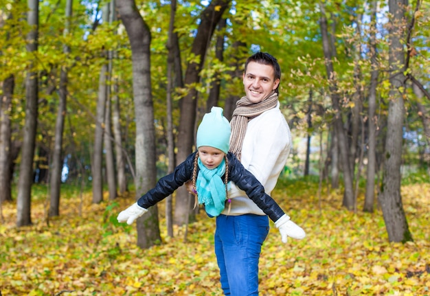 Happy dad and little daughter having fun in the park on sunny autumn day