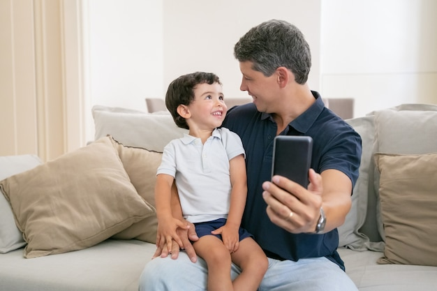 Happy dad and little son enjoying time together, sitting on couch at home, chatting, laughing and taking selfie.