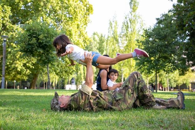 草の上に横たわって、まっすぐな手で娘を抱いて幸せなお父さん。かわいい女の子と遊ぶ白人の父。ママと男の子が近くに座っています。家族の再会、週末、帰国のコンセプト