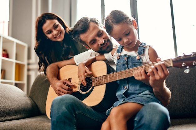 Happy dad and mom teach their cute little daughter to play the guitar while sitting on the sofa in the living room at home. the family spends time together.