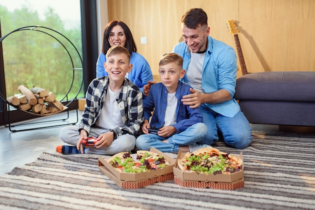 Happy dad mom and two sons sitting on floor playing video games with gamepads and eating tasty pizza