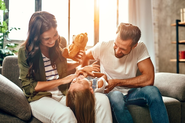Happy dad and mom with their cute daughter and teddy bear hug, play and have fun sitting on the sofa in the living room at home.