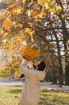 屋外で赤ちゃんと遊ぶ幸せなお父さん