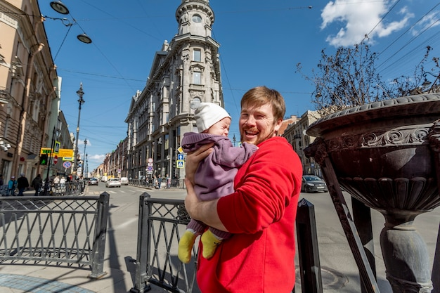 泣いている幼児と屋外でポーズをとる幸せなお父さん