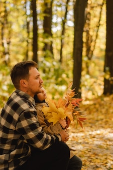 Happy dad and son are walking in the autumn forest autumn outdoor activity for family with kids